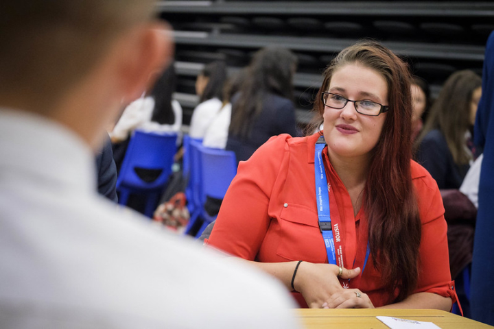 A female volunteer wearing a red shirt and blue NHS lanyard sits at a table with a student. Students show in the background sitting on blue chairs.